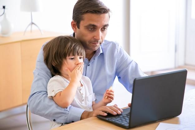 Gerichte vader met behulp van laptop en zoon op knieën te houden. blanke vader van middelbare leeftijd zittend aan tafel met schattige kleine jongen en werken op de computer. jeugd, freelance en vaderschap concept