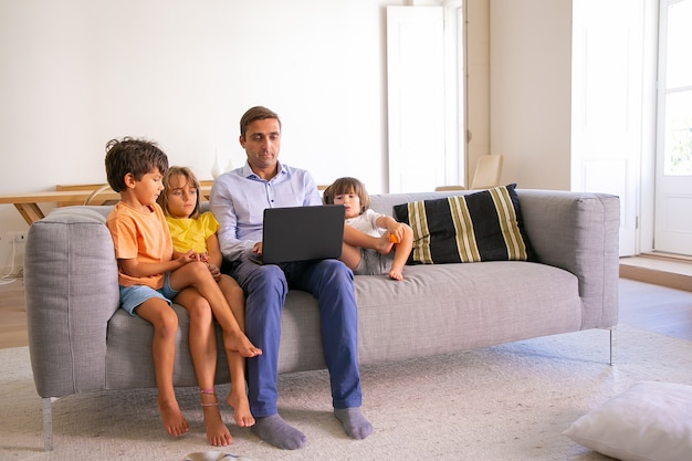 Gerichte vader van middelbare leeftijd zittend op de bank met kinderen en typen op laptop. kaukasische vader ontspannen met schattige kinderen in de woonkamer en film kijken. digitale technologie en vaderschap concept