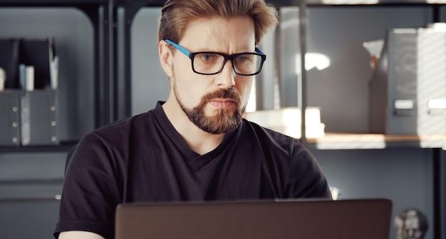 Gerichte volwassen man met behulp van computer werken vanuit kantoor aan huis tijdens lockdown vanwege virusepidemie