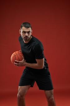 Gerichte vrolijke basketbalspeler die naar de fotocamera kijkt terwijl hij in actie is