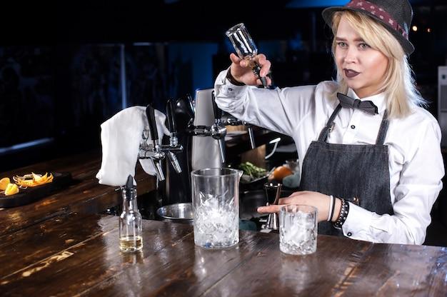 Gerichte vrouw barman formuleert een cocktail op de balk
