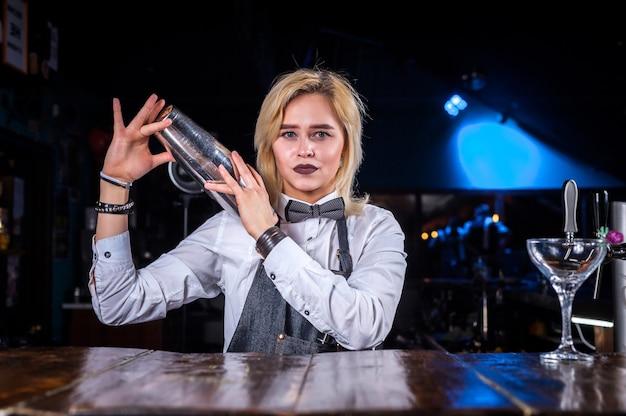 Gerichte vrouw bartending demonstreert zijn vaardigheden over de toonbank in de nachtclub