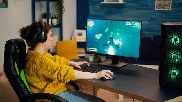 Gerichte vrouw gamer met headset die 's avonds laat een shooter online videogame op de computer in de woonkamer speelt. pro esport player streamer gaming-toernooi op rgb-computer, met behulp van moderne streamingtechnologie