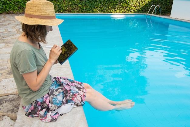 Gerichte vrouw in stro hoed zitten aan het zwembad
