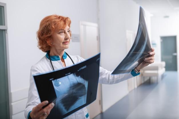 Gerichte vrouwelijke arts die x-ray scans van de longen van een patiënt onderzoekt
