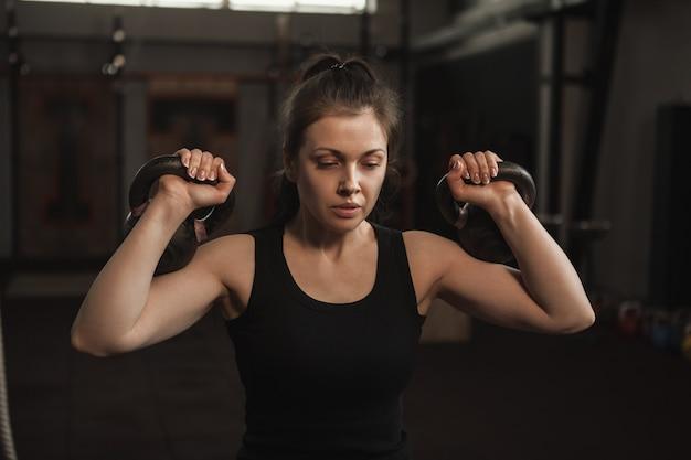 Gerichte vrouwelijke atleet trainen met kettlebells in de sportschool