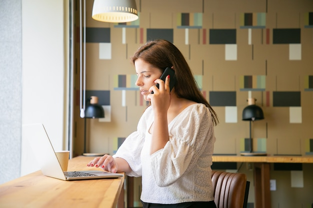 Gerichte vrouwelijke freelancer die op laptop werkt en op celtelefoon in co-werkruimte spreekt