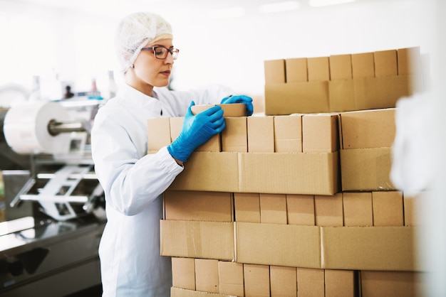 Gerichte vrouwelijke werknemer in steriele kleding is het tellen van dozen klaar voor levering.