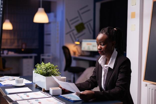 Gerichte workaholic jonge zakenvrouw die 's avonds laat werkt bij de presentatie van financiële grafieken van het bedrijf in de vergaderruimte