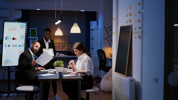 Gerichte workaholic ondernemersvrouw met donkere huid die managementstrategie uitlegt met behulp van tablet. zakelijk divers multi-etnisch teamwerk dat 's avonds laat overwerkt in de vergaderruimte van het bedrijfskantoor