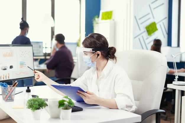 Gerichte zakenvrouw op een externe oproep met behulp van draadloze koptelefoons met gezichtsmasker tegen covid19. werknemers met vizieren die in de werkruimte van een bedrijfsbedrijf werken en de sociale afstandsanalyse respecteren