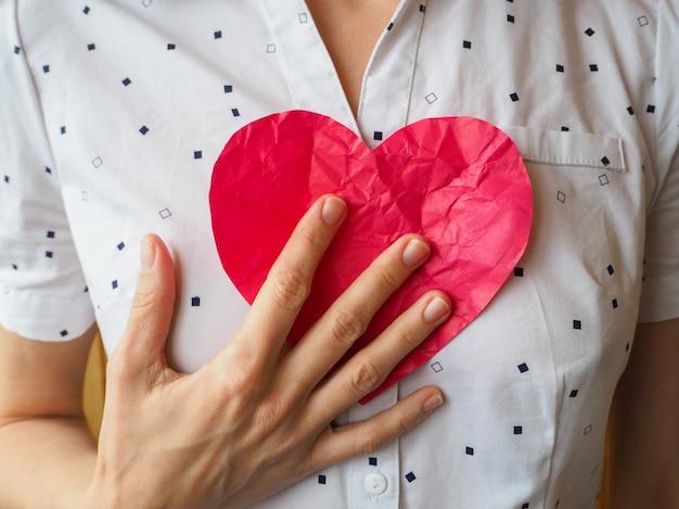 Gerimpeld hart in vrouwelijke handen. het symbool van een gebroken hart. valentijnsdag concept.