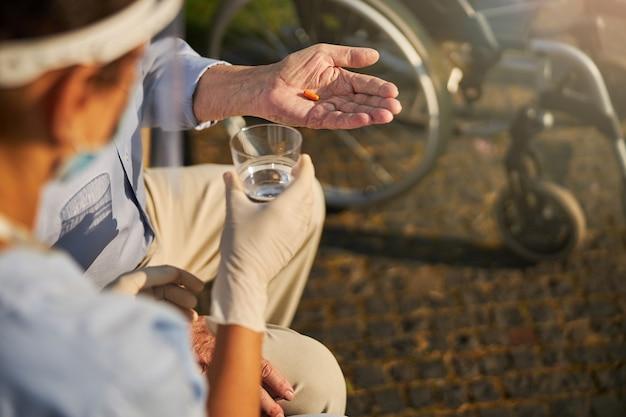 Gerimpelde hand met een antibioticum op een zonnige dag
