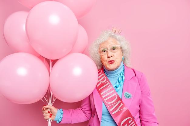 Gerimpelde mooie vrouw gekleed in feestelijke kleding houdt een stel opgeblazen ballonnen vast