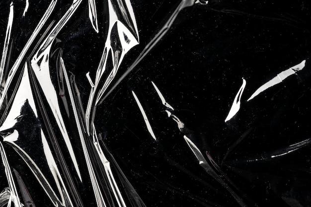 Gerimpelde plastic omslagtextuur op een zwart behang als achtergrond
