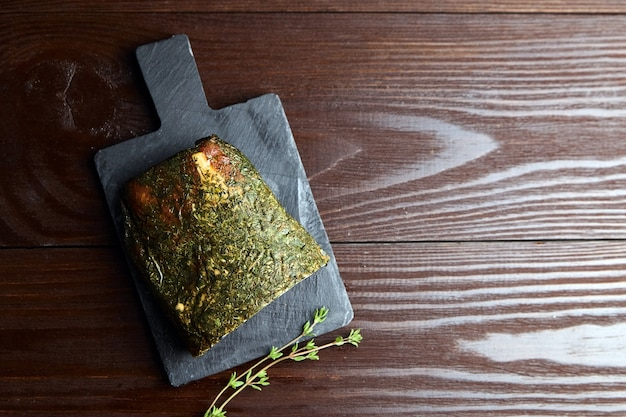 Gerky varkensvlees met kruiden en verse groene tijm op leisteen snijplank op houten tafel bovenaanzicht