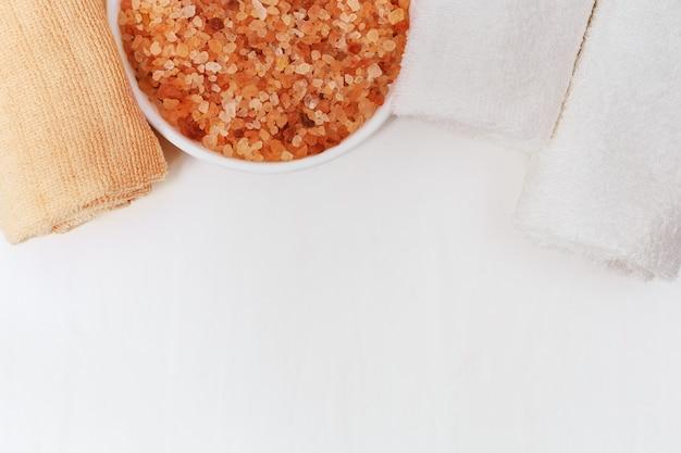 Gerolde badhanddoeken op concrete witte achtergrond. witte en oranje donzige handdoeken en oranje aromatisch zeezout voor bad. spa thema.