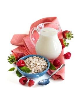 Gerolde haver in een kom met bessen en melk geïsoleerd op wit close-up