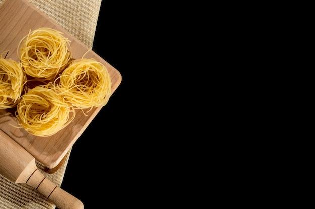 Gerolde tagliatelle vorm van italiaanse pasta op zwarte stenen achtergrond.