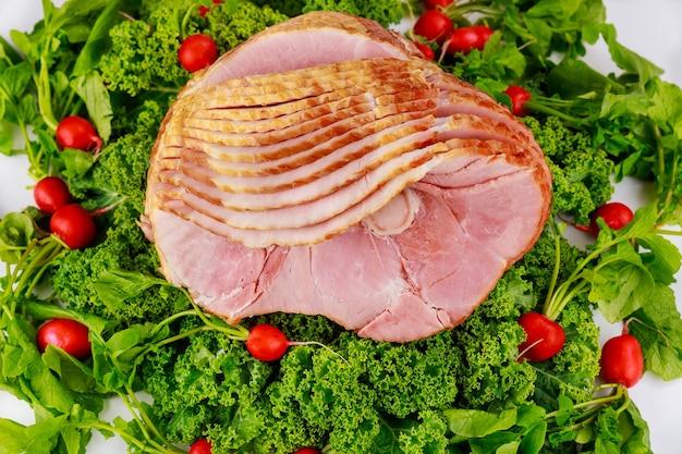 Gerookte en gesneden varkensham versierd met verse radijs en boerenkool.