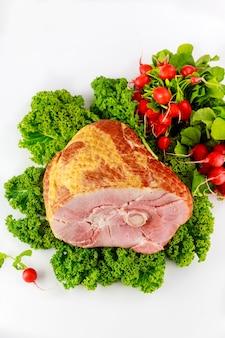 Gerookte en voorgesneden varkensham gedecoreerd met verse radijs en boerenkool.