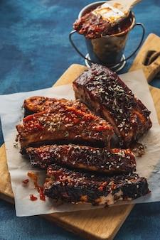 Gerookte geroosterde varkensribbetjes over blauw. barbecue gekruide ribben. traditioneel amerikaans bbq-eten