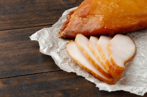 Gerookte kippenborst op bruin houten bord