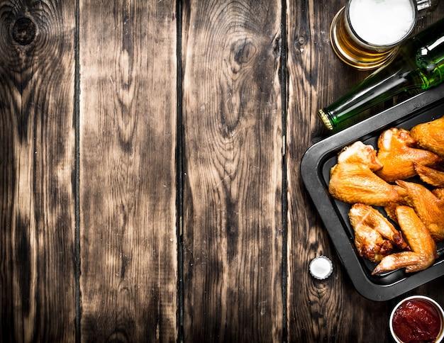 Gerookte kippenvleugels met bier en saus. op een houten tafel.
