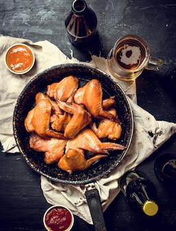 Gerookte kippenvleugels met bier. op zwart bord.
