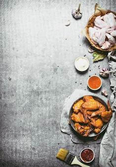 Gerookte kippenvleugels met saus. op een stenen ondergrond.