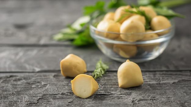 Gerookte mozzarellakaas in een glazen kom met kruiden op een houten tafel