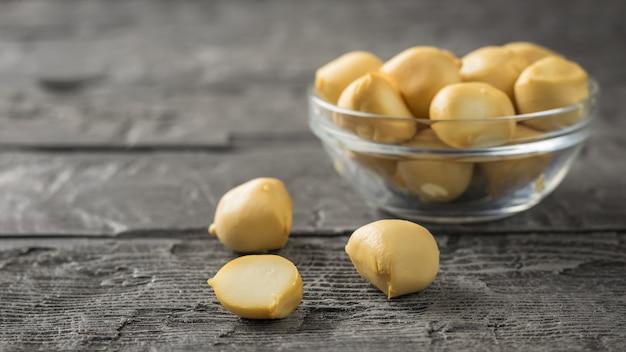 Gerookte mozzarellakaas in een glazen kom op een houten tafel