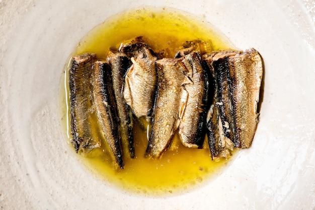 Gerookte sardines in olie geserveerd in witte keramische plaat. bovenaanzicht, plat gelegd. detailopname