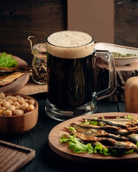 Gerookte sprot, gekookte kikkererwten geserveerd met een mok bier