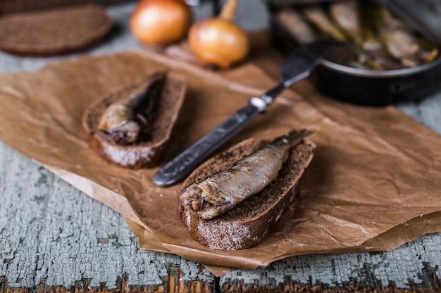Gerookte sprot met roggebrood op houten achtergrond wooden