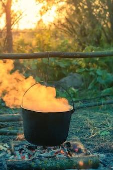 Gerookte toeristenketel boven kampvuur op de zonsondergang. proces van koken op de natuur. vintage gefilterd