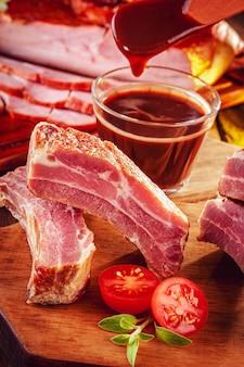 Gerookte varkensribbetjes met bbq saus en ingrediënten op een houten achtergrond - close-up