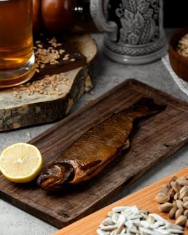 Gerookte vis geserveerd met citroen en bier