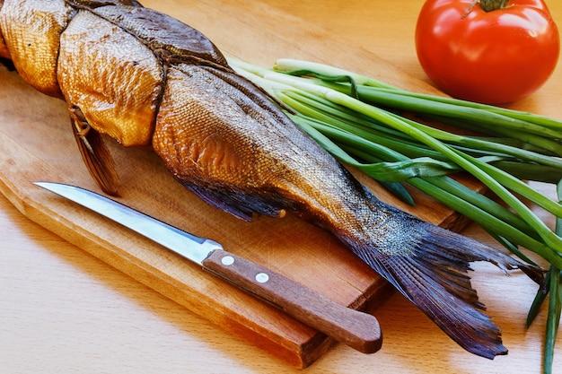Gerookte vis op een houten snijplank met groene uien en tomaat
