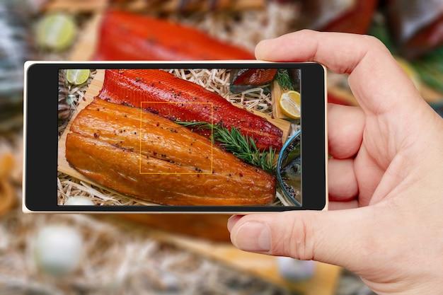 Gerookte vis op het smartphonescherm. verkoop van zeevruchten in een supermarkt. heerlijke delicatesse vis voor een feestelijke tafel.