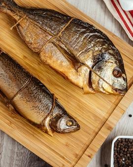 Gerookte vis op houten bord bovenaanzicht