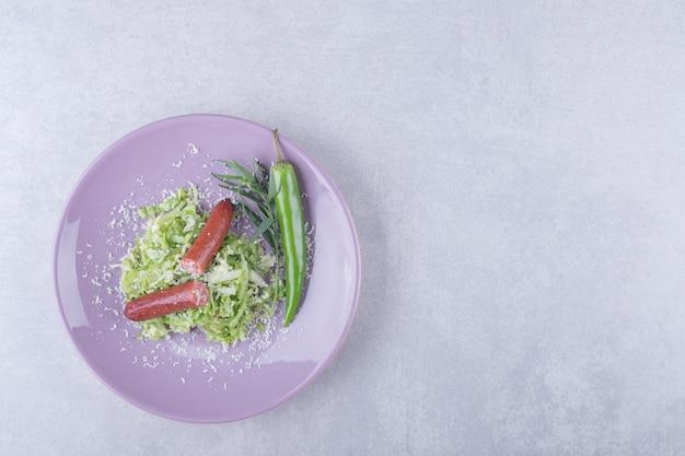 Gerookte worstjes en chilipeper op paarse plaat.