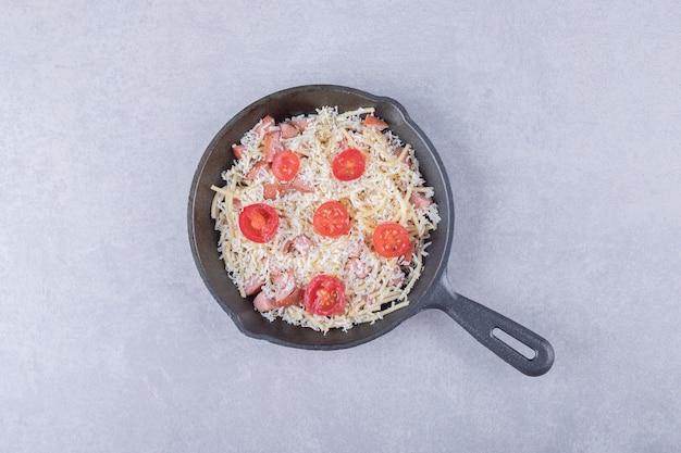 Gerookte worstjes en macaroni op zwarte pan.
