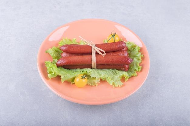 Gerookte worstjes vastgebonden met touw op oranje plaat.