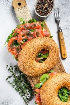 Gerookte zalm bagels sandwich met zachte kaas en rucola op een snijplank. witte achtergrond. bovenaanzicht.