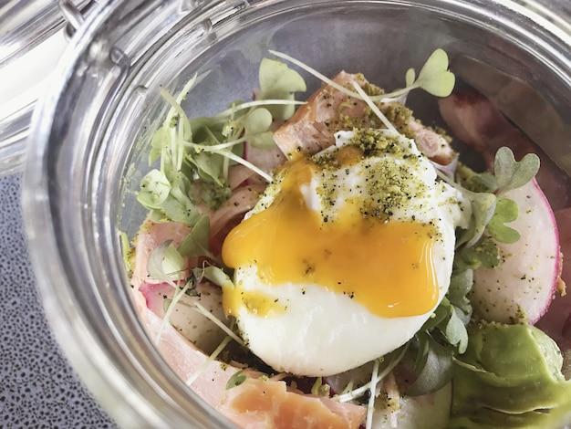 Gerookte zalm met gepocheerd ei en avocado in een pot