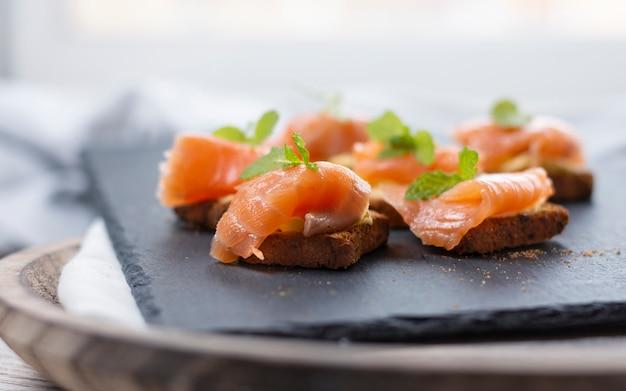 Gerookte zalm op toast met boter met muntblaadje op zwarte steen en oude houten plank
