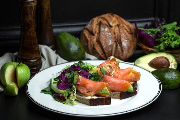 Gerookte zalmbruschetta met avocado en roomkaas geserveerd met salade