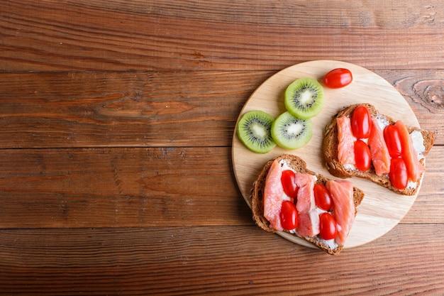 Gerookte zalmsandwiches met boter op houten achtergrond