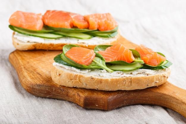 Gerookte zalmsandwiches met komkommer en spinazie op houten raad op een linnenachtergrond.
